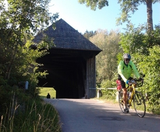 Riders coming thru covered bridge along the cycleway