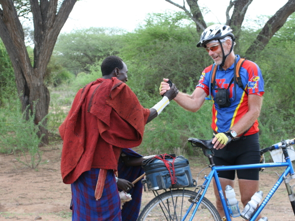 Brochure Tanzania old masaai shakes hands with rider