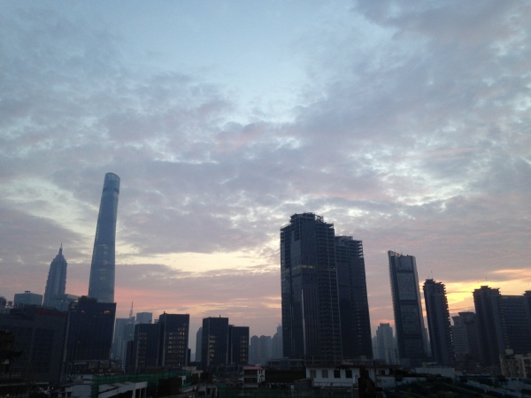 The sun peaks through the Shanghai skyline as riders prep for their first day of riding.
