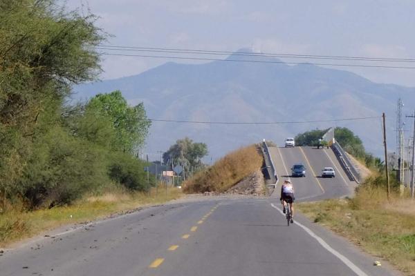 Beate rides towards the mountains near Guanajuato