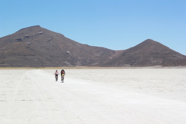 Kathy and Jean ride the salt flats with Tunapa Volcano in the background