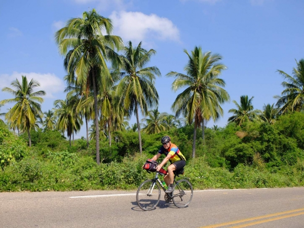 Wayne rides past palm trees in mainland Mexico