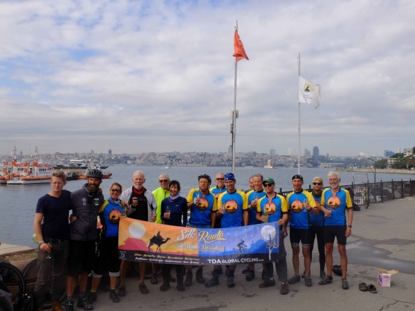Full tour riders, sectional, and staff line up on the bank of the Bosphorus