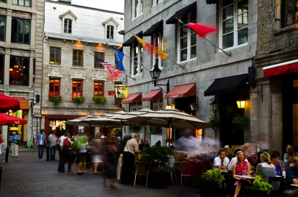 """Montreal, Canada - August 23, 2012: People dine on the patio of a restaurant along Rue Saint Vincent, while others mill around nearby, in the Old Montreal section of Montreal."""