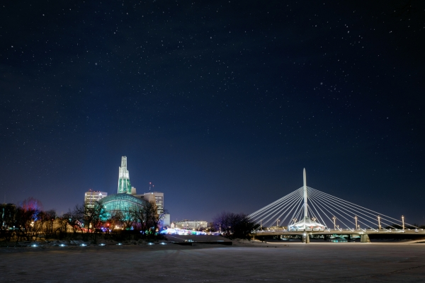 City of Winnipeg skyline at night in winter.  Esplanade RIel and the Canadian Museum for Human Rights in view.