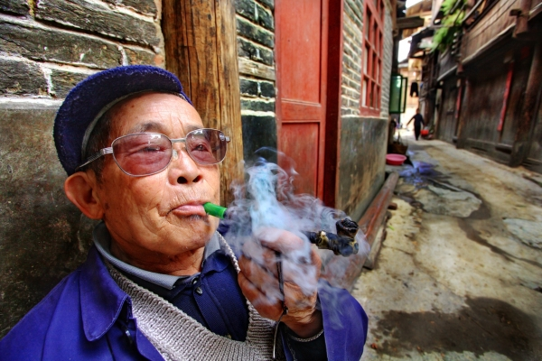 """Zhaoxing village, Guizhou province, China - April 9, 2010:  An elderly Chinese farmer wearing glasses, smoking a pipe outside his home April 9, 2010. Zhaoxing Dong villages, Liping County. Chinese peasant produces tobacco smoke."""