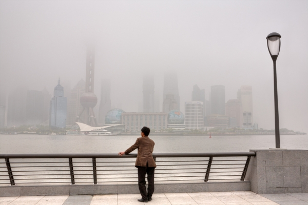 Shanghai, China - April 20, 2010: Air Pollution, high-rises shrouded in heavy smog,  air in City remained severely polluted, man standing on the Bund, and looks at the Pudong District.